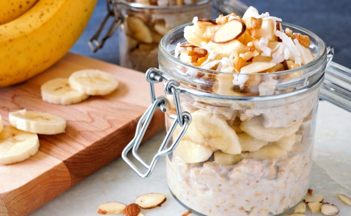 Healthy overnight oats with bananas and nuts in glass canning jars